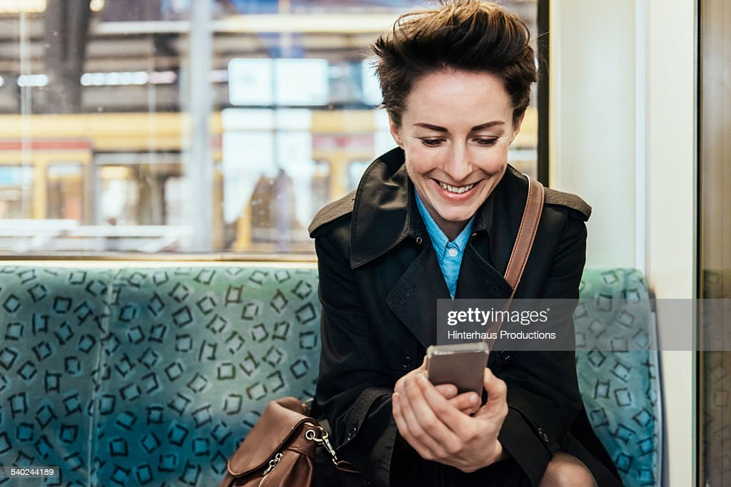 Businesswoman With Smart Phone In Commuter Train : Photo