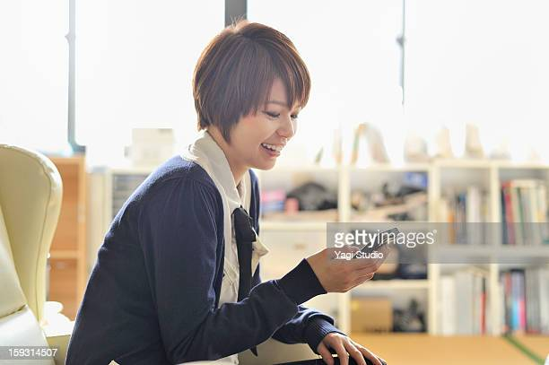 Businesswoman with smartphone in the office