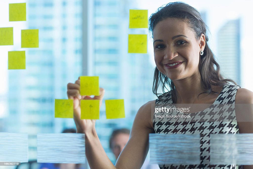 Businesswoman with sticky note on window : Stock Photo