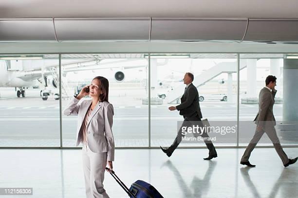 Geschäftsfrau mit Koffer am Flughafen