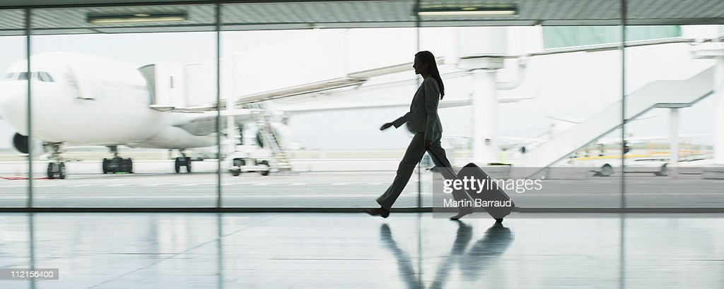 Businesswoman with suitcase in airport : Stock Photo