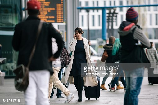 Businesswoman with suitcase using Smartphone