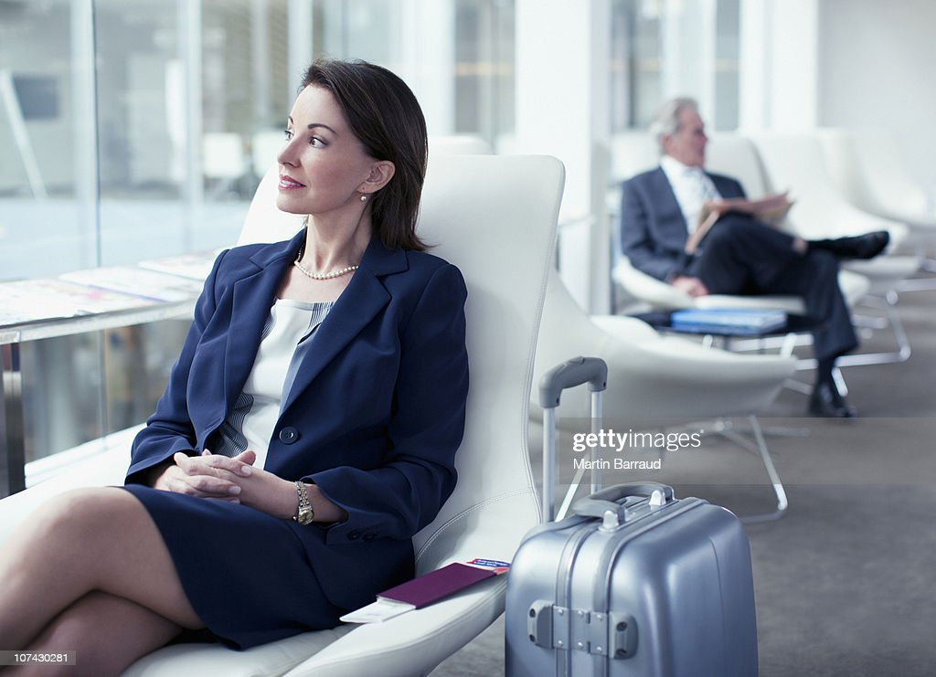 Businesswoman with suitcase waiting in airport : Stock Photo