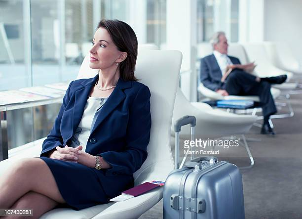 Businesswoman with suitcase waiting in airport