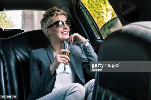 Femme d'affaires avec lunettes de soleil en limousine avec champagne