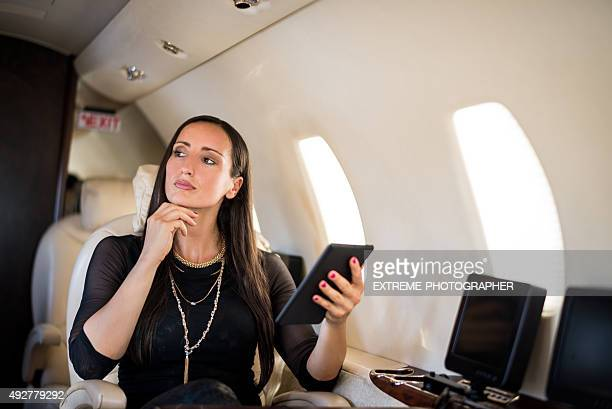 Businesswoman with tablet in private jet airplane