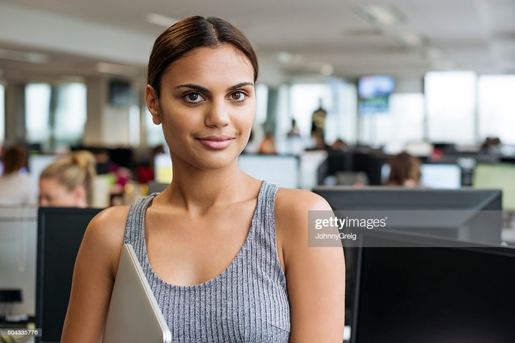 Businesswoman with tablet smiling towards camera in modern office : Stock Photo