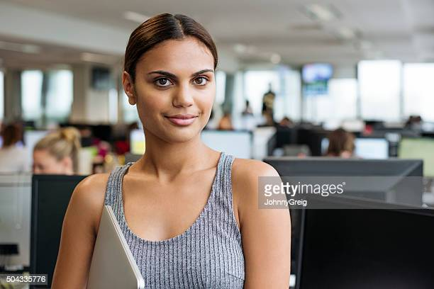 Businesswoman with tablet smiling towards camera in modern office