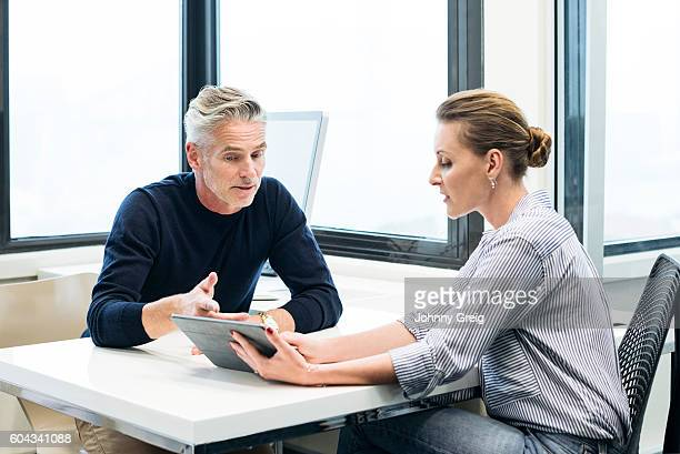 Businesswoman with tablet working together with mature man in office