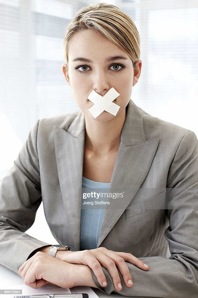Businesswoman with tape covering mouth : Stock Photo
