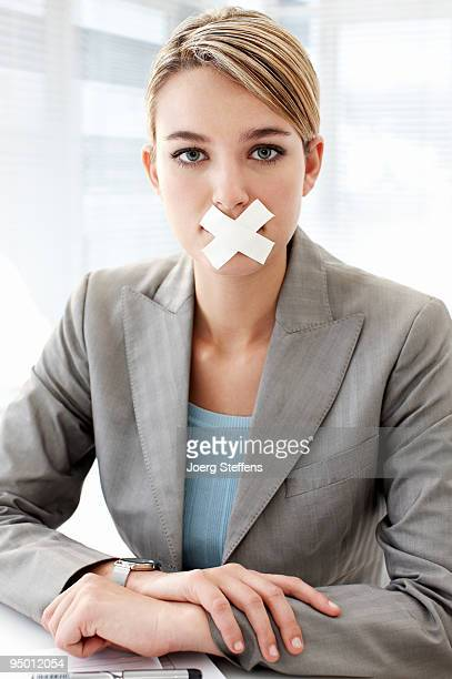Businesswoman with tape covering mouth