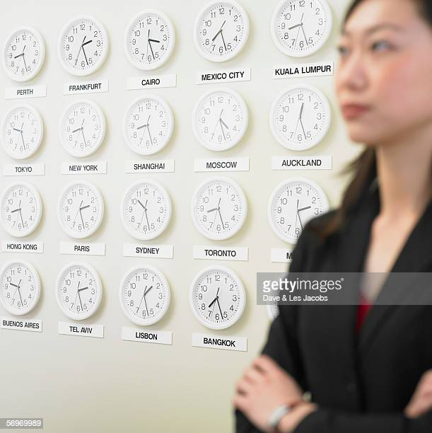 Businesswoman with time zone clocks on the wall behind her