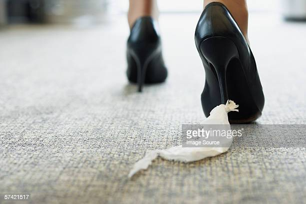 Businesswoman with toilet paper stuck to her shoe