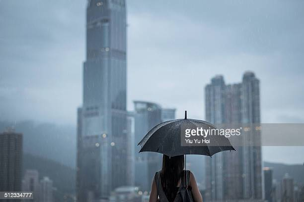 Businesswoman with umbrella looking away at city