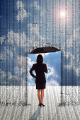 Businesswoman with umbrella under stock market prices