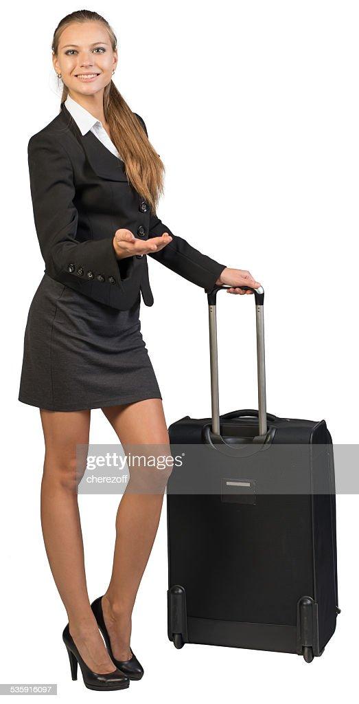 Mulher de negócios com rodas Mala, mostrando algo, olhando para a Câmera, a sorrir : Foto de stock