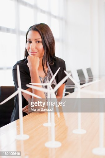 Businesswoman with wind turbine models in office : Stock Photo