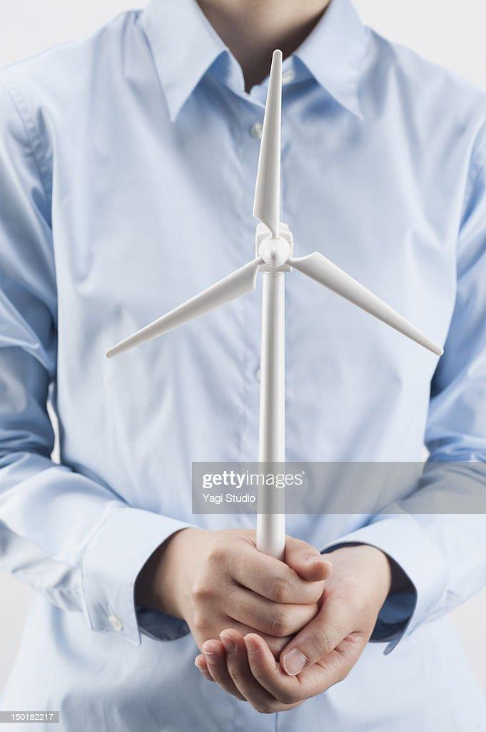 Businesswoman with wind turbine models : Stock Photo
