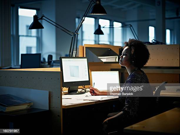 Businesswoman working at desk at night