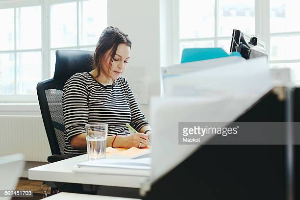 Businesswoman working at desk in creative office