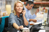 Businesswoman Working At Desk In Warehouse On The Phone