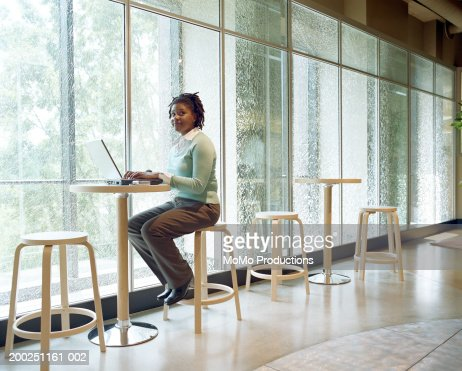 Businesswoman working at laptop by opaque windows : Stock Photo