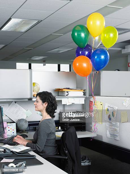 Businesswoman working in cubicle, celebratory ballons behind her