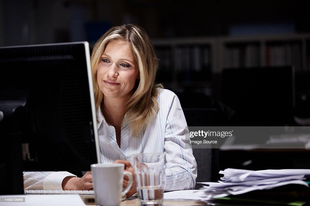 Businesswoman working in dark office : Stock Photo