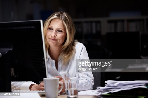 Businesswoman working in dark office : Bildbanksbilder