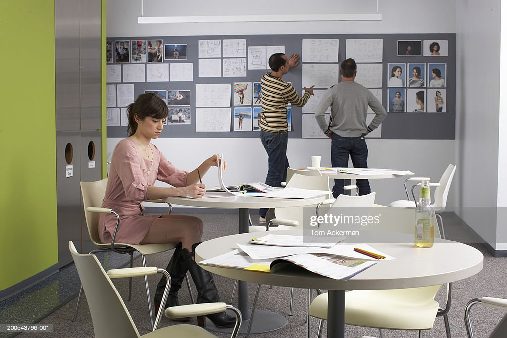 Businesswoman working in lunchroom, men talking by wall in background : Stock Photo