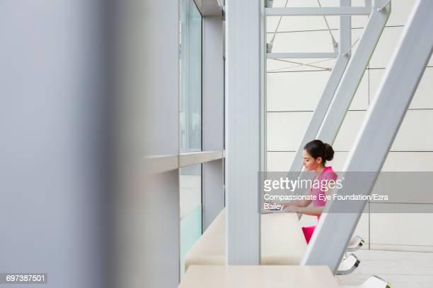Businesswoman working in modern lobby