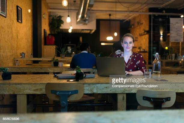 Businesswoman working late using laptop in cafe