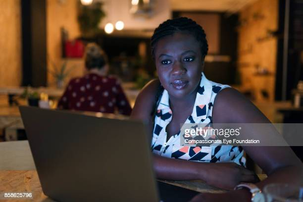Businesswoman working late with laptop in cafe