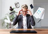 Businesswoman working on a laptop, overworking, under pressure
