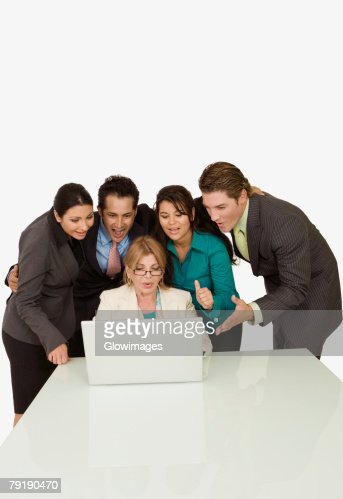 Businesswoman working on a laptop with four business executives standing beside her : Foto de stock