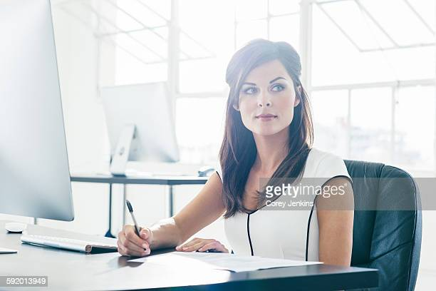 Businesswoman working on computer by office window