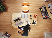 Businesswoman working on computer in office, talking on phone, overhead view