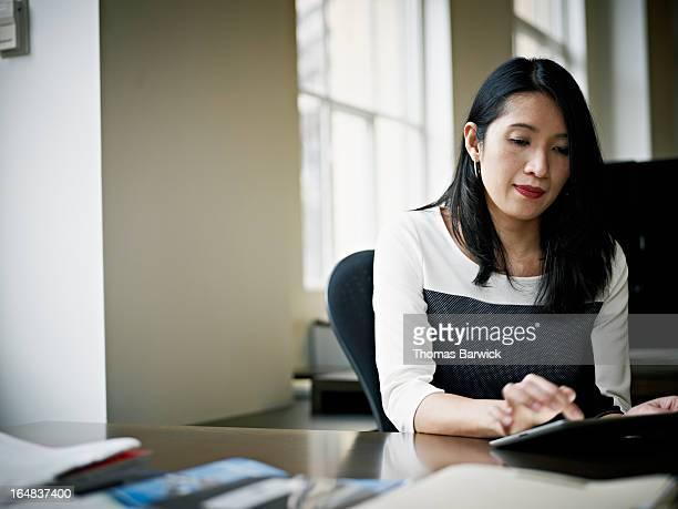 Businesswoman working on digital tablet at desk