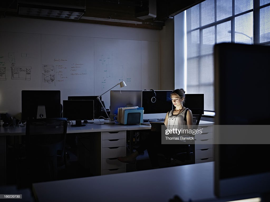 Businesswoman working on digital tablet at night