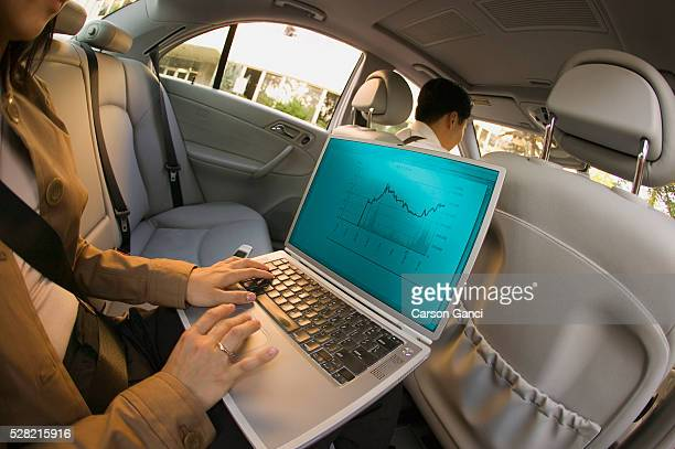 Businesswoman Working on Laptop in Car