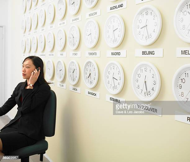 Businesswoman working with time zone clocks on the wall behind her