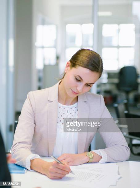 businesswoman works at desk in office, writing into document
