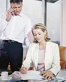 Businesswoman writing at desk, male colleague using phone in background