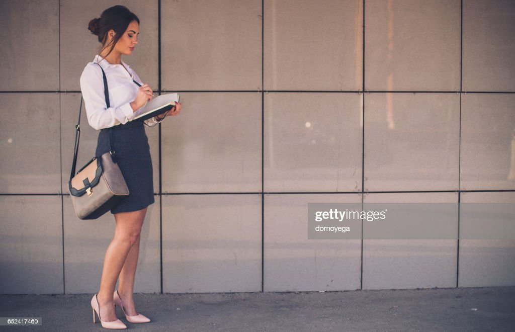 Businesswoman writing her busy schedule in the note book : Stock Photo