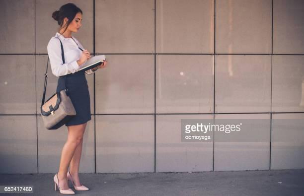 Femme d'affaires écrit son horaire chargé dans le carnet de notes