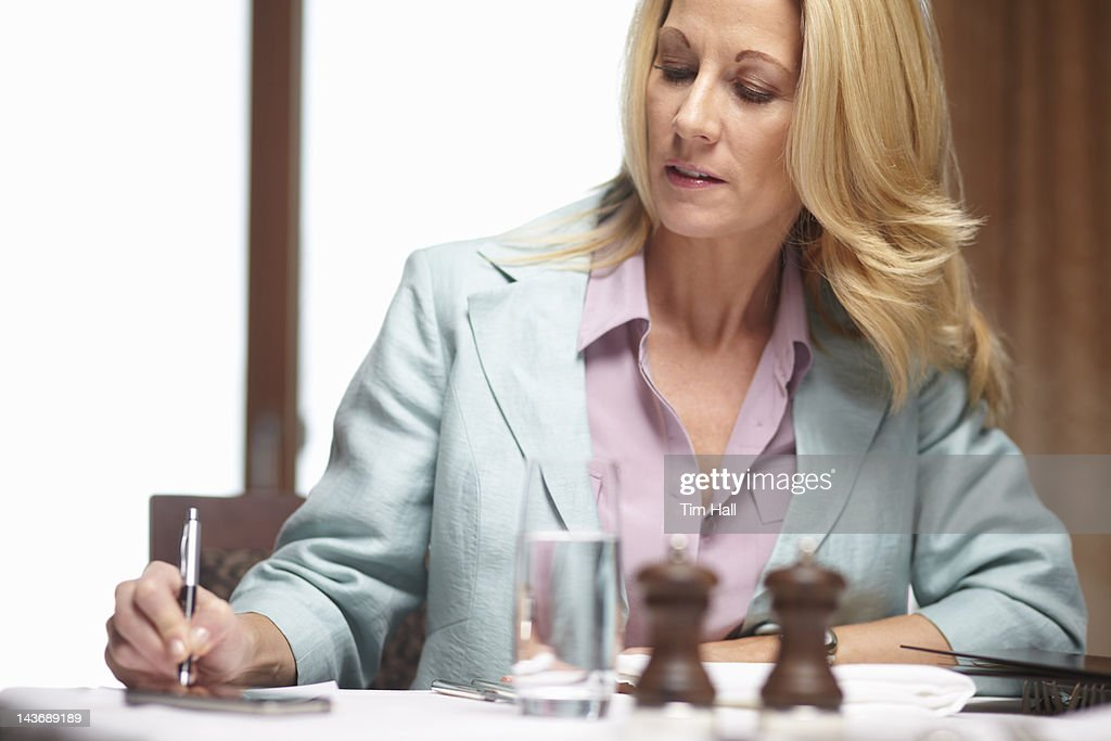 Businesswoman writing in cafe : Stock Photo