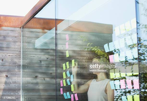 Businesswoman writing on adhesive notes attached to office window