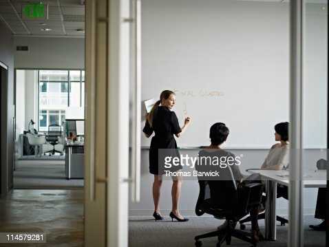 Businesswoman writing on board in conference room : Stock Photo