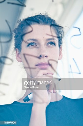 Businesswoman writing on glass