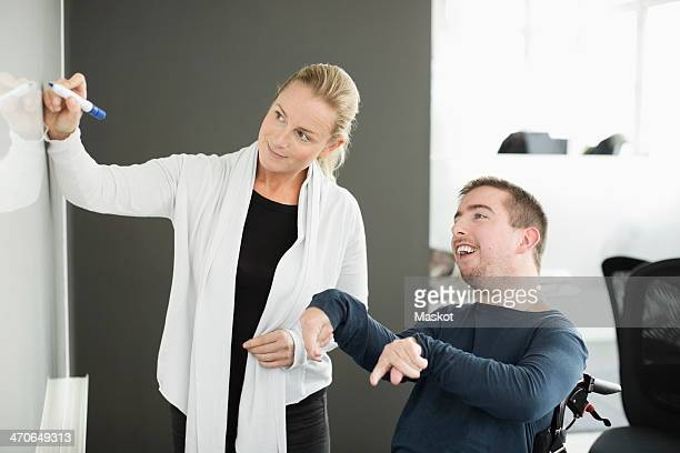 Businesswoman writing on whiteboard while working with disabled businessman in office